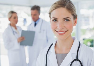 Smiling blonde haired doctor standing in her office with colleagues working behind