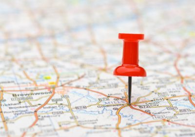 Red pushpin marking a location on a road map, selective focus