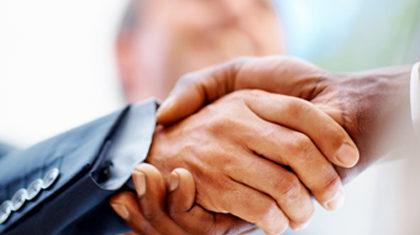 Closeup: Business men shaking hands over a deal
