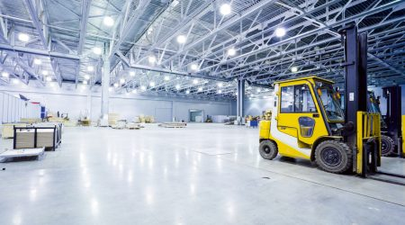 empty room of modern storehouse with forklift truck loader on a foreground